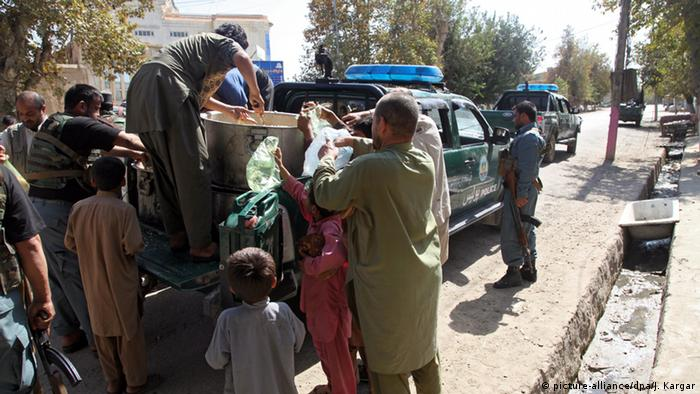 Local residents receive food distributed by Police as Afghan security forces try to regain control of the city, in Kunduz, Afghanistan, 04 October 2015. (Photo: EPA/JAWED KARGAR)