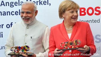 German Chancellor, Angela Merkel, right, and Indian Prime Minister Narendra Modi smile after receiving souvenirs depicting the logo of 'Make in India' campaign during their visit to German engineering company Bosch's vocational centre in Bangalore, India, Tuesday, Oct. 6, 2015 (AP Photo/Aijaz Rahi)