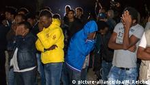 05.10.2015 *** dpatopbilder Flüchtlinge trauern am 05.10.2015 in Saalfeld (Thüringen) nach einem Brand mit einem Todesopfer in einem Asylbewerberheim. Die Todesursache des Mannes war zunächst unklar. Foto: Michael Reichel/dpa +++(c) dpa - Bildfunk+++