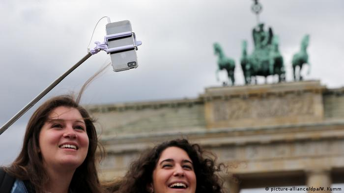female tourists with a selfie-stick in front of Gate Brandenburg in Berlin, Germany , Copyright: Wolfgang Kumm/dpa