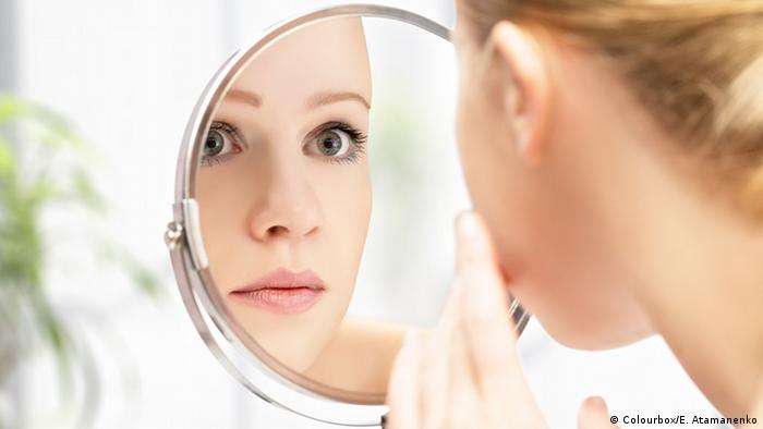 woman with immaculate skin staring into mirror (Colourbox/E. Atamanenko)