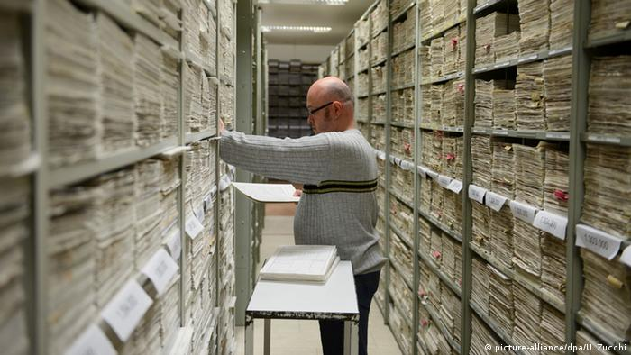 Homem durante trabalho dentro dos Arquivos de Arolsen