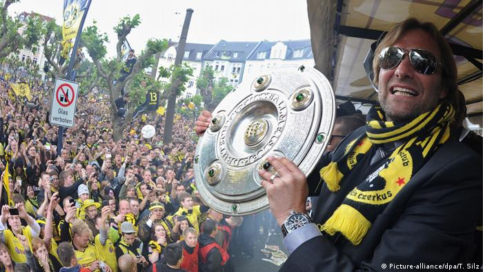 Jürgen Klopp holding the Bundesliga title (Picture-alliance/dpa/T. Silz)