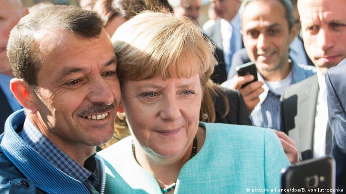 Angela Merkel und ein Flüchtling posieren für ein Selfie (Foto: dpa)