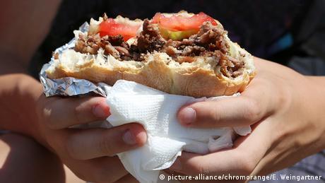 Zwei Hände halten eine angebissene Brottasche, die mit Fleisch, Tomaten und etwas Grünem gefüllt ist.