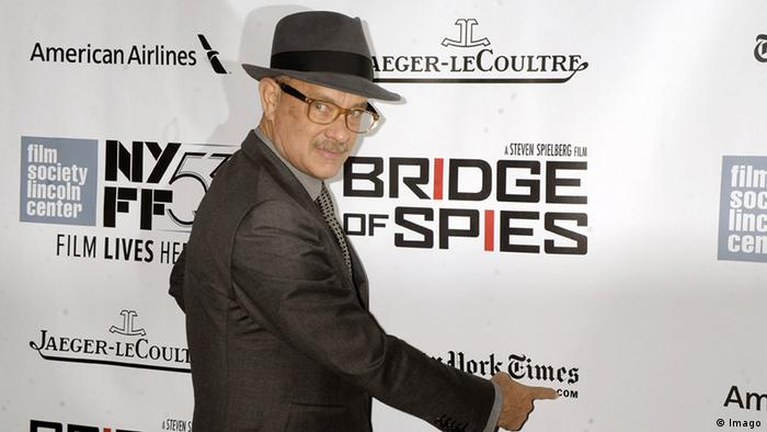 Premiere of Bridge of Spies with Tom Hanks wearing a hat and glasses an pointing to sign with the title of the movie