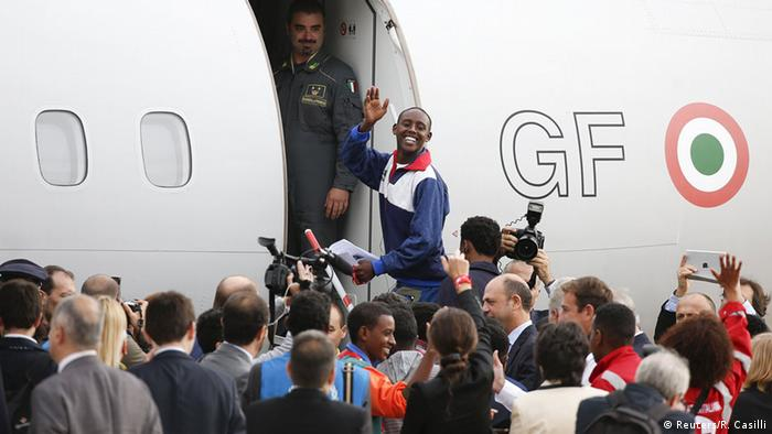 Refugees from Eritrea climb on board a plane in Rome to be resettled in Sweden