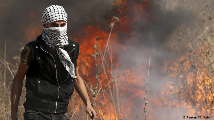 Ein vermummter Palästinenser geht an einem brennenden Feld vorbei (Foto: rtr)