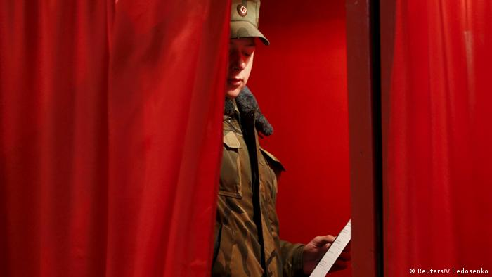 A Belarussian serviceman holds a ballot in a voting booth