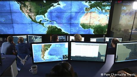 A number of screens show images of Earth from the NASA EOS control room