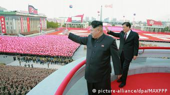 North Korean leader Kim Jong Un (front) and Liu Yunshan, the Chinese Communist Party's fifth-ranked leader, wave to the crowd from a balcony overlooking Kim Il Sung Square in Pyongyang during a military parade on Oct. 10, 2015, to mark the 70th anniversary of the founding of the ruling Workers' Party (Photo: Kyodo)