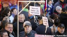 12.10.2015+++ People hold up a mock hangman's gallows with a sign reading 'Reserved for Sigmar Gabriel' (L) and 'Reserved for Angela Merkel' as they gather for an anti-immigration demonstration organised by rightwing movement Patriotic Europeans Against the Islamisation of the West (PEGIDA) in front of the Palace Church in Dresden, Germany October 12, 2015. Sigmar Gabriel is the German minister of Economy. Picture taken October 12, 2015. REUTERS/Hannibal Hanschke