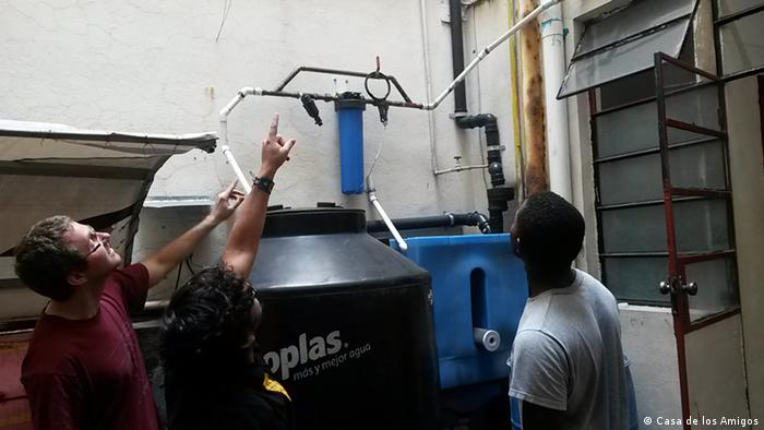 Volunteers and employees of guesthouse Casa de los Amigos inspect their newly-installed rainwater harvester
