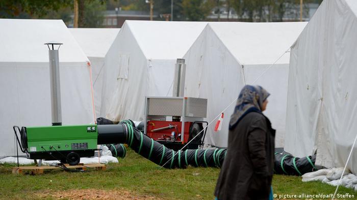 Трубы тянутся к палаткам от работающего отопительного генератора в лагере для беженцев