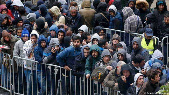 Migrants queue in the compound outside the Berlin Office of Health and Social Affairs (LAGESO) as they wait to register in Berlin