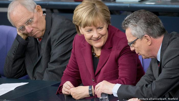 German Chancellor Angela Merkel smiling at Interior Minister Thomas de Maiziere with Wolfgang Schäuble in the background
