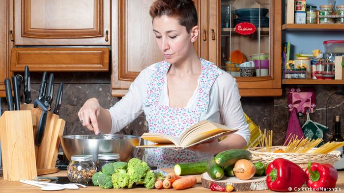 Eine Frau steht in einer Küche, hält ein Kochbuch in der linken Hand und rührt mit der rechten in einem Topf. Vor ihr liegen unterschiedliche Gemüse.