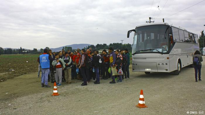 Refugees stand next to a bus near the Macedonian border