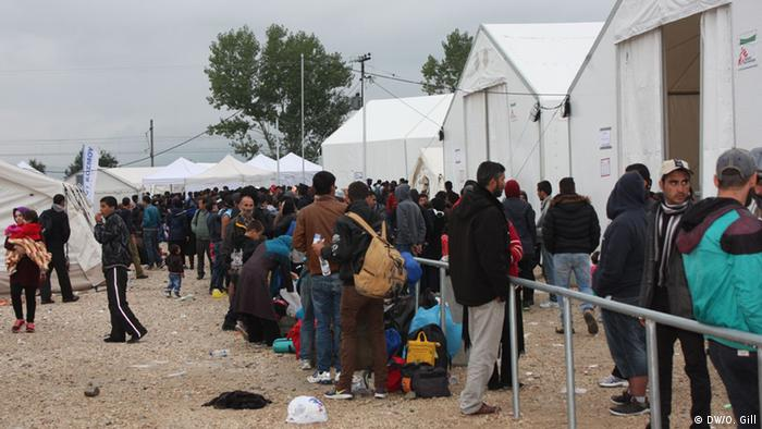 Refugees stay in large tents at the border until their turn comes to cross