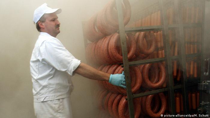 Man and sausage links in smokehouse (picture-alliance/dpa/M. Schutt)