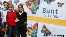 ARCHIV - Vor der Villa Kunterbündnis in Güstrow (Mecklenbug-Vorpommern) steht am 19.04.2015 Geschäftsführerin Karen Larisch (r, Die Linke), um gemeinsam mit anderen gegen einen Aufmarsch der MVgida zu protestieren, auf dem Banner steht Bunt statt braun. Am 20.08.2015 besucht der Landesvorsitzende von Bündnis 90/Die Grünen, Katz, im Zuge seiner Sommertour die Villa Kunterbündnis. Foto: Bernd Wüstneck/dpa +++(c) dpa - Bildfunk+++