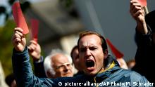People hold red cards as they protest against a demonstration by the right-wing Alternative for Germany (AfD) party against the uncontrolled immigration and asylum abuse in Freilassing, Germany, Saturday, Oct. 17, 2015. (AP Photo/Matthias Schrader)
