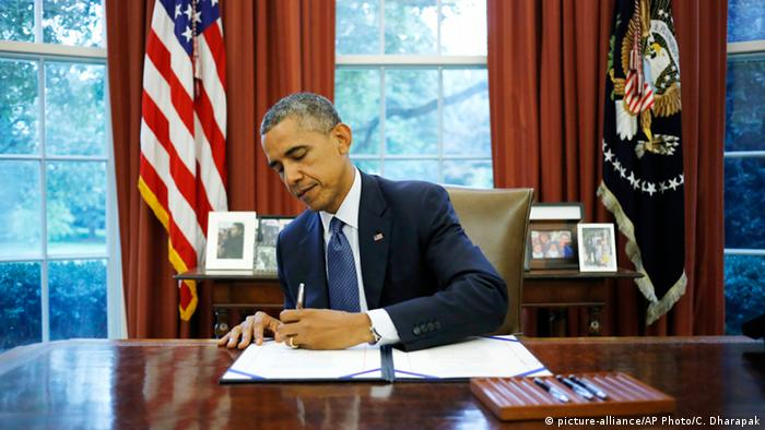 US President Barack Boama signs a law at his desk in the Oval Office (picture-alliance/AP Photo/C. Dharapak)