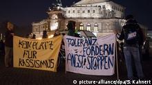 Gegner des islamkritischen Pegida-Bündnisses stehen am 09.03.2015 auf dem Theaterplatz in Dresden (Sachsen) vor der Semperoper und halten zwei Transparente mit der Aufschrift Kein Platz für Rassismus und Toleranz fördern, Angst stoppen. Die Patriotischen Europäer gegen die Islamisierung des Abendlandes (Pegida) haben wieder zu einer Kundgebung in Sachsens Landeshauptstadt aufgerufen. Foto: Sebastian Kahnert/dpa +++(c) dpa - Bildfunk+++