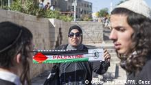 17.05.2015 **** Bildunterschrift: A Palestinian woman holds a scarf bearing the colours of the Palestinian flag as young Israeli nationalists gather outside Damascus Gate in Jerusalem's old city on May 17, 2015, to take part in the 'flag march' to mark the 48th anniversary of the capture of Arab east Jerusalem in the Six Day War of 1967. Known as Jerusalem Day, the anniversary marks Israel's seizure and later annexation of the territory, which includes the walled Old City, in a move never recognised by the international community. AFP PHOTO / JACK GUEZ (Photo credit should read JACK GUEZ/AFP/Getty Images)