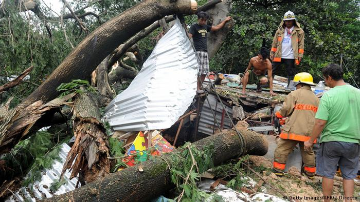 Fallen trees and debris block roads, impeding disaster relief efforts