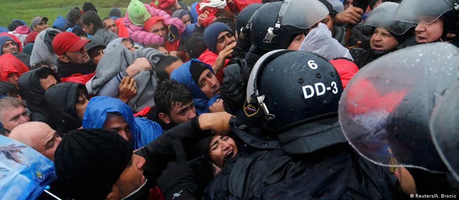 Migrantes tentam entrar num ônibus na Eslôvenia que os levaria até a Áustria