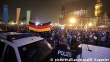 Pegida-Demonstranten haben sich am 19.10.2015 in Dresden (Sachsen) versammelt. Vor einem Jahr war Pegida (Patriotische Europäer gegen die Islamisierung des Abendlandes) in Dresden erstmals auf die Straße gegangen. Foto: Michael Kappeler/dpa