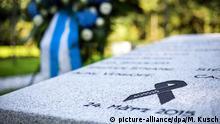 Eine Schleife mit der Flugnummer 4U9525 ist am 21.08.2015 in Haltern am See (Nordrhein-Westfalen) an der Gedenkstätte für die Opfer der Flugkatastrophe vom 24. März 2015 auf dem Kommunalfriedhof zu sehen. Im Hintergrund steht ein großer Blumenkranz. Am 21.08.2015 soll die Einsegnung einer weiteren Gedenkstätte für die Opfer des Germanwings-Absturzes stattfinden. Damit erinnert die Stadt an die 16 Schüler und zwei Lehrerinnen des Gymnasiums, die bei dem Absturz im März 2015 ums Leben kamen. Eine Woche zuvor ist eine weitere Gedenkstätte an der Schule übergeben worden. Foto: Marcel Kusch/dpa +++(c) dpa - Bildfunk+++