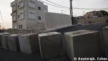 A street view shows concrete cubes that were placed last week (foreground), and according to Israel, a newly erected temporary concrete wall that measures around 10 meters, in Jerusalem October 18, 2015. Israel erected what it said as a temporary concrete wall along a short stretch of a street that on one side is a Jewish neighbourhood and the other is the outskirts of Jabel Mukabar, a Palestinian neighbourhood which has been one of the flashpoints of the recent flare-up of violence in Jerusalem. Israeli police spokeswoman Luba Samri said the short section of barrier was intended to prevent petrol bombs being thrown at the apartments in the Jewish neighbourhood on Meir Nakar street. REUTERS/Amir Cohen