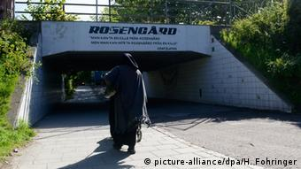 A woman approaches an underpass marked with a sign reading Rosengaard