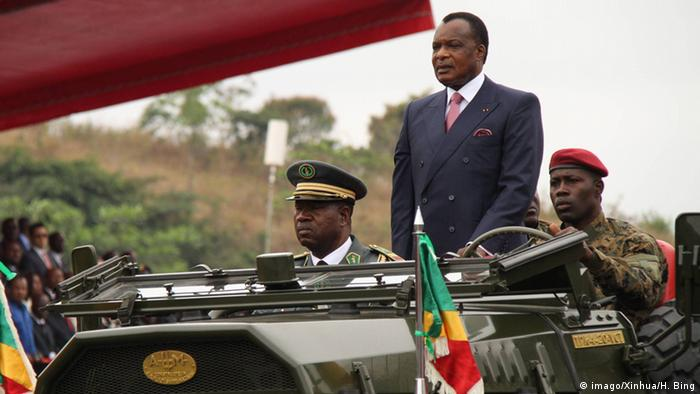 President Denis Sassou N'Guesso stands up in the back of an armed jeep, with a military sldier driving and an officer riding shotgun.