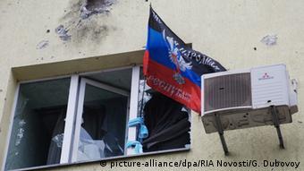 Флаг ДНР в окне с разбитыми стеклами