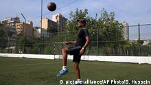 Former Trinidad and Tobago midfielder David Nakhid, who last week submitted his candidacy to FIFA to stand in February's emergency presidential election, plays football on a playground during a training session for children in Beirut, Lebanon, Sunday, Oct. 18, 2015. (AP Photo/Bilal Hussein)