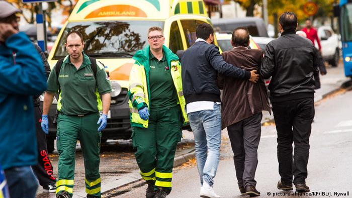 People walk away from the scene of a sword attack in Sweden