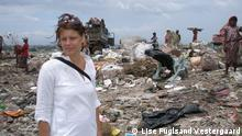 A woman stands in front of a pile of trash
