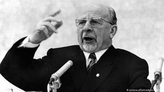 Homem de paleto e gravata, cavanhaque branco, semicalvo e de óculos gesticulando ao microfone