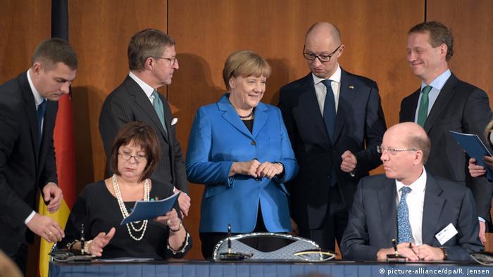 Анґела Меркель і Арсеній Яценюк у момент підписання міжурядових документів на конференції у Берліні