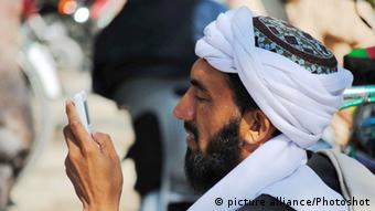 Man looking at his mobile phone in Pakistan (photo: picture alliance)