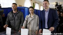25.10.2015 (R-L) Mayor of Kiev Vitaly Klitschko, his wife Natalia and his brother World heavyweight champion Wladimir Klitschko pose for a picture while casting their ballots during a regional election at a polling station in Kiev, Ukraine, October 25, 2015. Ukrainians go to the polls on Sunday to appoint mayors and council heads to regional seats. Copyright: Reuters/V. Ogirenko