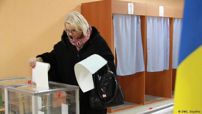 Женщина бросает бюллетень в избирательную урну на одном из избирательных участков в Киеве 25 октября