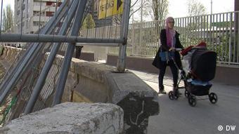 A woman pushes a pram past a construction site