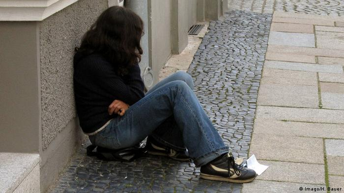 Teenage girl sitting on the sidewalk begging. (Photo: Imago/Heike Bauer)