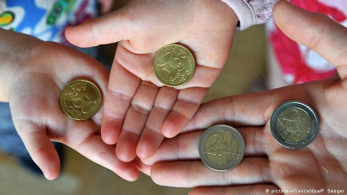 Kids' hands holding euro coins (picture-alliance/dpa/P. Seeger)