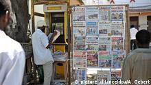 20. April 2010 Mehrere Männer stehen am 20.04.2010 an einer Straße in Stonetown, der Altstadt von Sansibar, vor einer Stellwand, an der eine aktuelle Tageszeitung aushängt. picture-alliance/dpa/A. Gebert