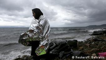 An Afghan refugee standds on a Greek beach after arriving on a raft